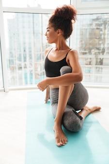 Vrij gezonde vrouw die moeilijke oefening op vloer maakt