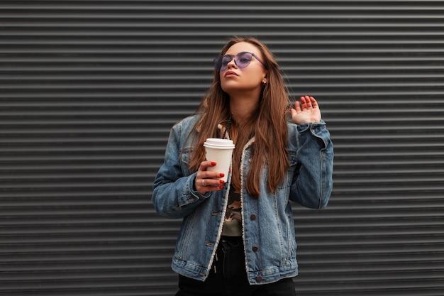 Vrij glamoureuze stedelijke jonge vrouw model in trendy paarse bril in stijlvol denim jasje met kopje warme drank poseren in de buurt van metalen wand buitenshuis. amerikaans hipstermeisje met koffie geniet van een wandeling.