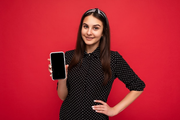 Vrij glimlachend gelukkig donkerbruin meisje dat geïsoleerd over een rode muur staat en casual stijlvolle zwarte kleding draagt