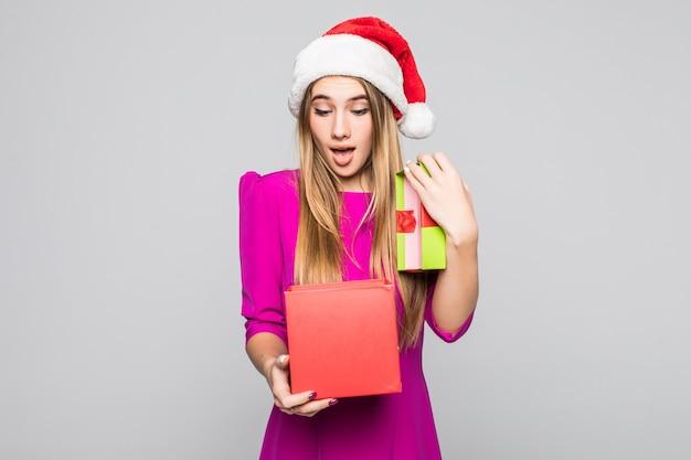 Vrij glimlachend grappig gelukkig meisje in korte roze jurk en nieuwjaarshoed houden kartonnen doos verrassing in haar handen