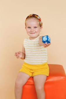 Vrij glimlachend meisje, gezeten op oranje stoel