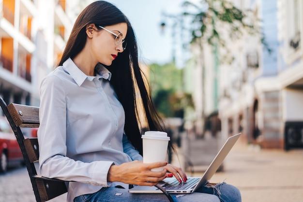 Vrij glimlachend terloops gekleed studentenmeisje zittend buiten op een bank genieten van haar koffie en werken met behulp van laptop