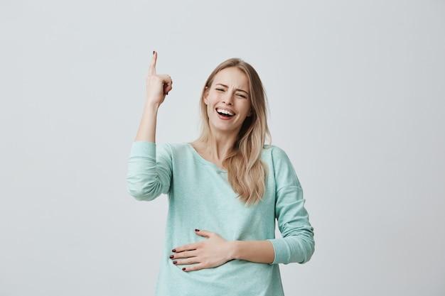 Vrij glimlachend vreugdevolle vrouw met geverfd blond haar, wijsvingers omhoog wijzend, met kopie ruimte