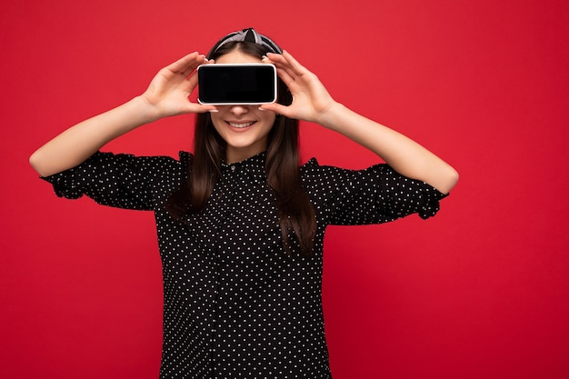 Vrij glimlachend vrolijk donkerbruin meisje dat zich geïsoleerd over rode muur bevindt die toevallige modieuze zwarte kleren draagt die mobiele telefoon met leeg scherm voor uitsparing tonen.