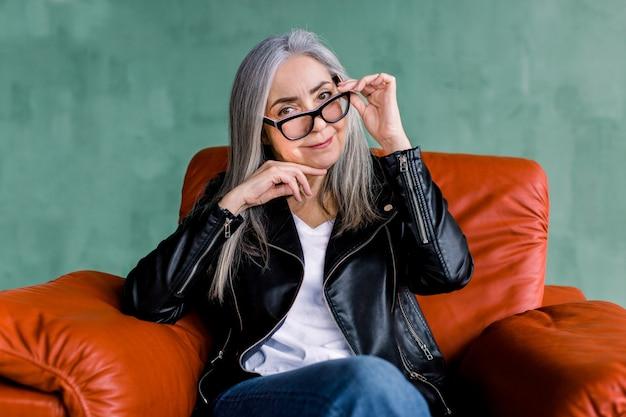 Vrij glimlachende 60-jarige senior dame met lang recht grijs haar, kijkend naar de camera