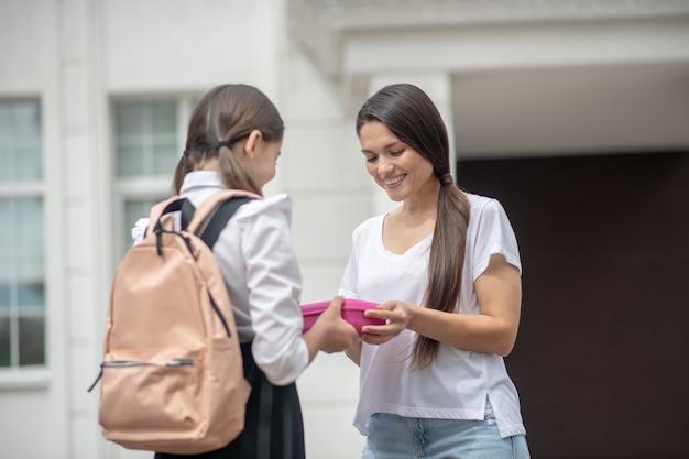 Vrij glimlachende jonge volwassen vrouw die lunchbox geeft aan langharige schoolmeisje met rugzak dichtbij school