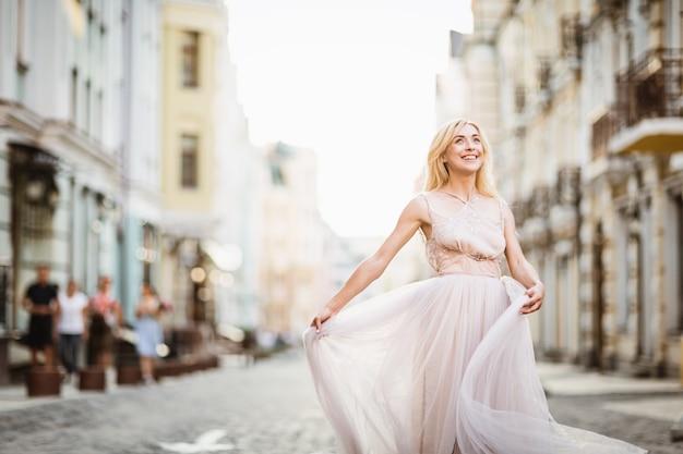 Vrij glimlachende jonge vrouw met lang blond haar in elegante vliegende lichte kleding die langs de straat loopt