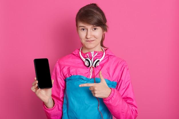 Vrij glimlachende kaukasische vrouw in blauw en roze sportoverhemd dat het lege smartphonescherm toont en haar vinger op telefoon richt