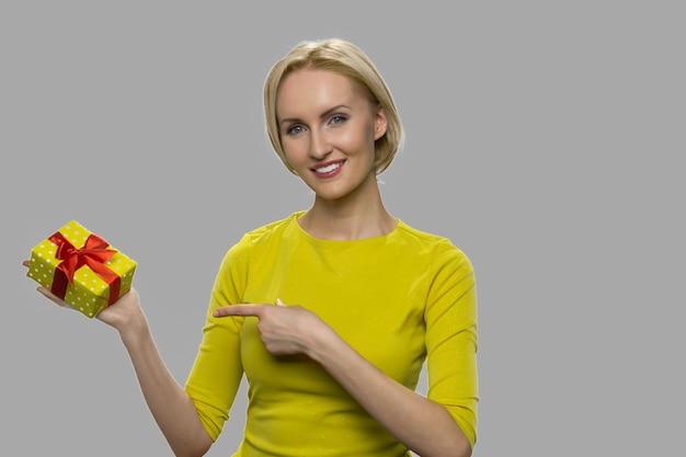 Vrij glimlachende vrouw die giftdoos in haar hand toont. aantrekkelijke vrouw die met vinger op giftdoos richt tegen grijze achtergrond. ruimte voor tekst.