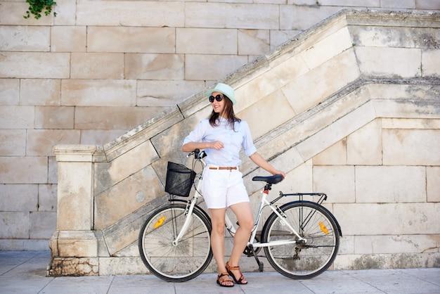 Vrij glimlachende vrouw die op fiets op witte steenmuur en tredenachtergrond leunen op heldere zonnige dag