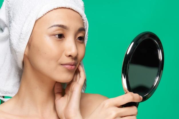 Vrij glimlachende vrouw met een spiegel in haar handen een handdoek op haar hoofd groene huidzorg.