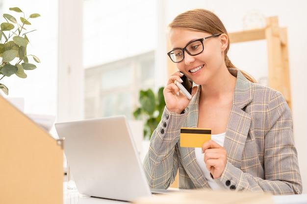 Vrij goed geklede zakenvrouw praten met online winkel manager op mobiele telefoon terwijl laptop scherm kijken