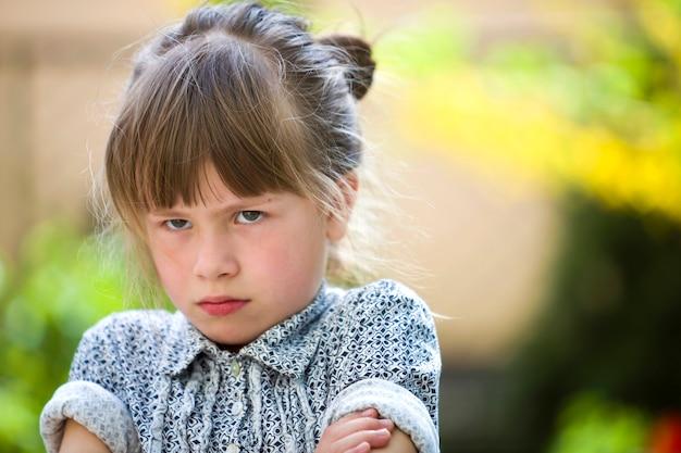 Vrij grappig humeurig jong kindmeisje openlucht die boos en ontevreden op vage groene zomer voelen. kinderen driftbui.