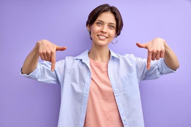 Vrij grappige dame wijst vinger naar beneden op lege ruimte die product adviseert voor kopers, kopieer ruimte. geïsoleerde paarse achtergrond