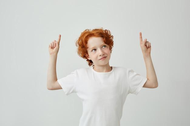 Vrij grappige kleine gemberjongen met sproeten die bovenkant met vingers op beide handen richt, licht glimlachend.