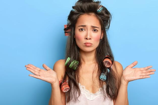 Vrij het jonge vrouw stellen met haarkrulspelden