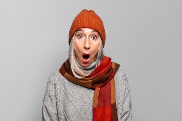 Vrij hogere vrouw die de winterkleren draagt. koud concept