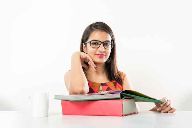 Vrij indiase aziatische collage meisje studeren op tablet met stapel boeken