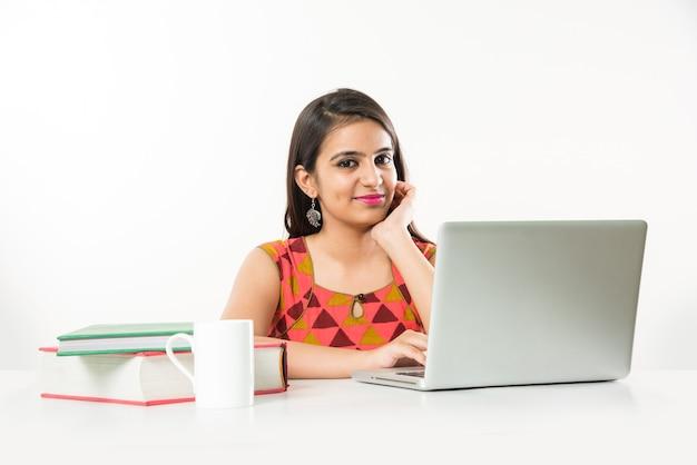 Vrij indiase aziatische meisje studeren op laptopcomputer met stapel boeken op tafel, op witte achtergrond