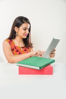 Vrij indiase aziatische meisje studeren op tabletcomputer met stapel boeken op tafel, op witte achtergrond