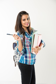 Vrij indiase of aziatische jonge universiteitsmeisje met boeken en tas terwijl ze geïsoleerd op een witte achtergrond staat