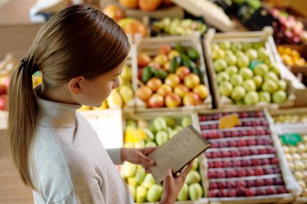 Vrij jeugdig meisje in casual pullover kijken door boodschappenlijst in kladblok terwijl staande