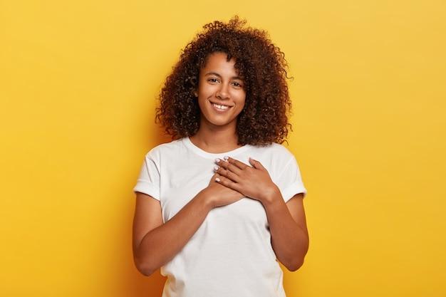 Vrij jong afro-amerikaans vrouwtje houdt palmen dichtbij het hart, drukt zijn dankbaarheid uit