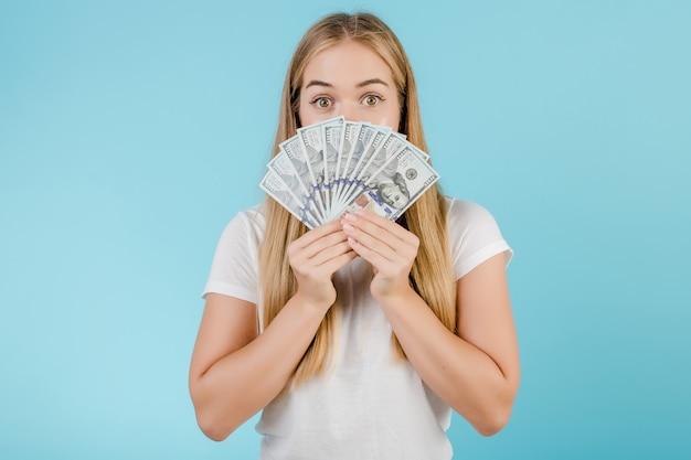 Vrij jong blondemeisje met dollardrekeningen dat over blauw wordt geïsoleerd