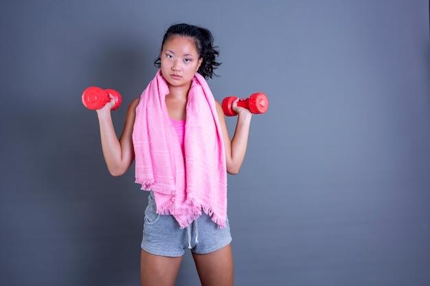 Vrij jong chinees meisje dat traint met halters die recht vooruit kijken
