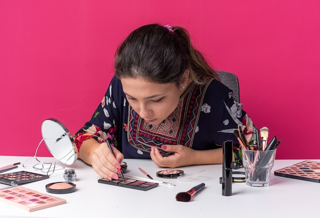 Vrij jong donkerbruin meisje dat aan tafel zit met make-uptools die eyeliner vasthouden en naar het oogschaduwpalet kijken