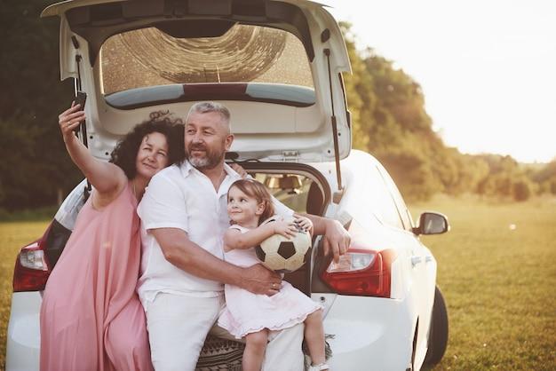 Vrij jong echtpaar en hun dochter rusten in de natuur. de vader van de moeder en het meisje zitten op open kofferbak