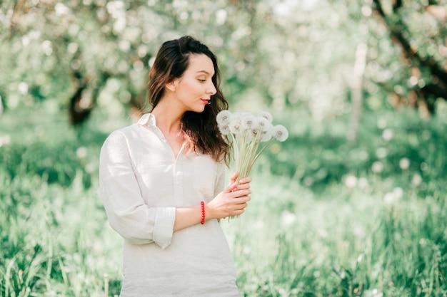 Vrij jong gelukkig donkerbruin meisje in wit overhemd met emotioneel vrolijk gezicht die, in de lente bloeiende tuin glimlachen met boeket van paardebloemen. cute vrouwelijke model poseren in de natuur