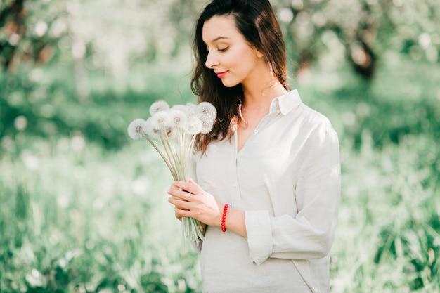 Vrij jong gelukkig donkerbruin meisje in wit overhemd met het emotionele vrolijke gezicht glimlachen, die als kind in de lente bloeiende tuin lachen met boeket van paardebloemen. cute vrouwelijke model poseren in de natuur
