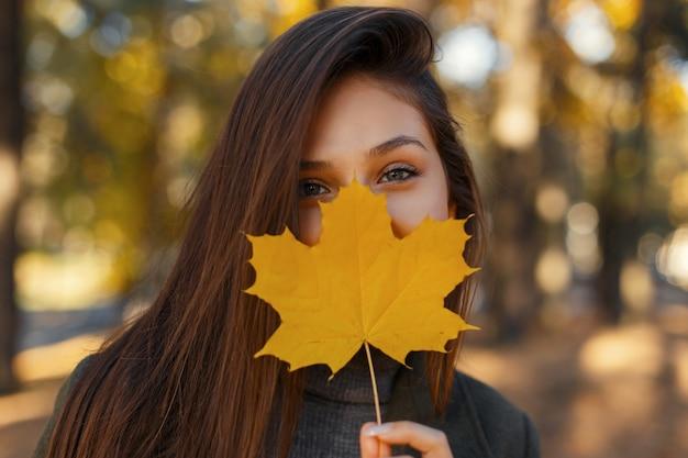 Vrij jong gelukkig meisje met een glimlach bedekt haar gezicht met een goudgeel herfstblad op de natuur