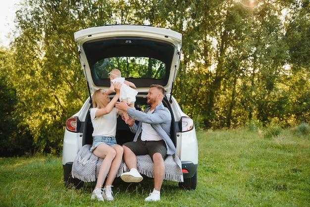 Vrij jong getrouwd stel en hun dochter rusten in de natuur. de vrouw en het meisje zitten op de open kofferbak.