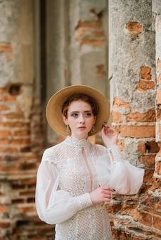 Vrij jong kaukasisch roodharigemeisje in een tuin en buiten met haar huwelijksboeket. mooie roodharige bruid.