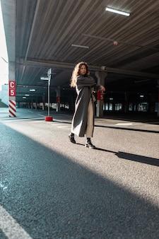 Vrij jong krullend meisje in modieuze stadskleren met een lange jas en een stijlvolle handtas loopt in de stad op de parkeerplaats