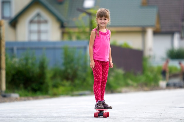Vrij jong langharig blond kindmeisje dat in vrijetijdskleding tribune op skateboard glimlacht