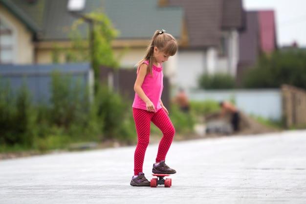 Vrij jong langharig blond kindmeisje die in vrijetijdskleding tribune op het concept van de skateboard vn glimlachen.
