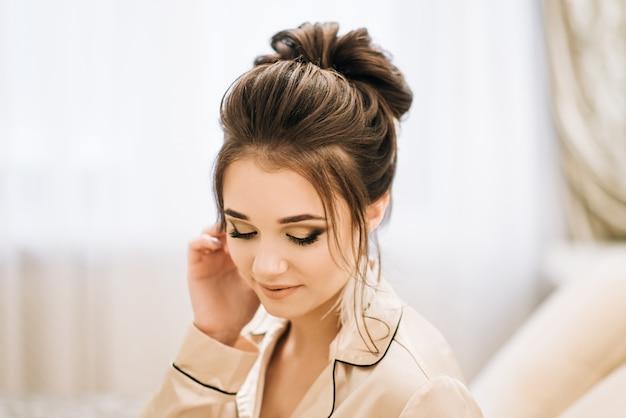 Vrij jong meisje. boudoirochtend van de bruid. bruid met luxe haren en make-up. accessoires met veren