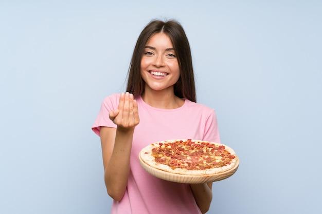 Vrij jong meisje dat een pizza over geïsoleerde blauwe muur houdt die met hand uitnodigt te komen. blij dat je bent gekomen