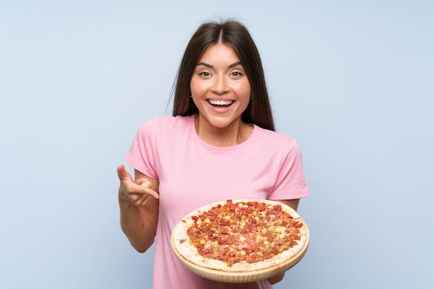 Vrij jong meisje dat een pizza over geïsoleerde blauwe muur houdt