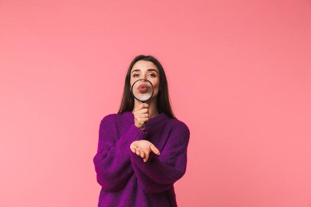 Vrij jong meisje dat sweater draagt die zich geïsoleerd over roze bevindt, door een vergrootglas kijkt, kus verzendt