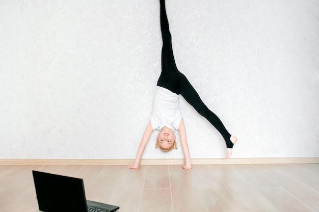 Vrij jong meisje die in sportkleding online video op laptop letten en thuis geschiktheidsoefeningen doen. training op afstand met personal trainer, sociale afstand of zelfisolatie, online onderwijsconcept