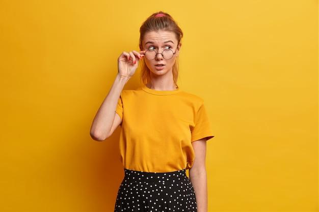Vrij jong meisje hoort verbazingwekkende geruchten, houdt de hand op de brilrand, draagt een geel t-shirt, een rok met stippen, kijkt weg met verbazing en achterdocht