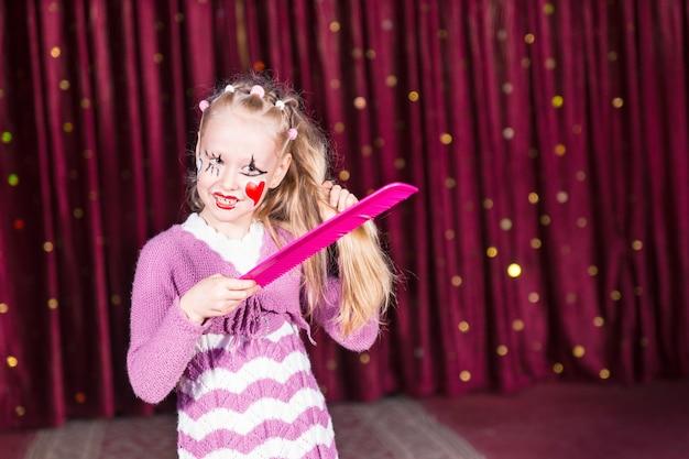 Vrij jong meisje in een roze pantomimekostuum dat op het podium staat en haar lange blonde haar kamt met een buitenmaatse kam in haar kleurrijke make-up en gezichtsverf