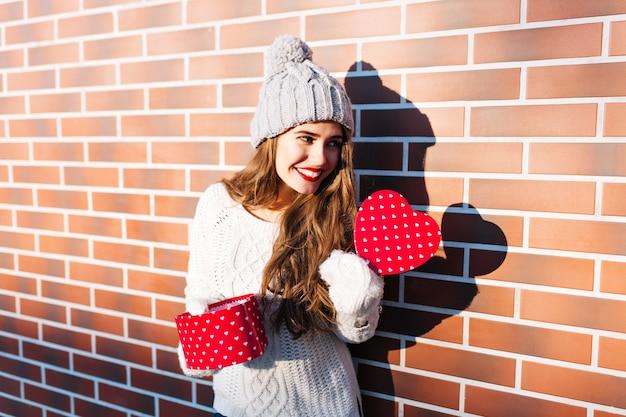 Vrij jong meisje in gebreide muts, warme trui en handschoenen op muur buiten. ze houdt een open dooshart in haar handen, glimlachend naar de andere kant.