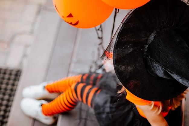 Vrij jong meisje in halloween-kostuum als een heks die op de trap van het huis zit en een bos oranje ballonnen vasthoudt. de nadruk ligt op de hoed. halloween-concept.