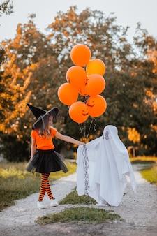 Vrij jong meisje in kostuum als een heks poseren met kleine jongen jurken als grappige geest op straat met oranje ballonnen. partijconcept.