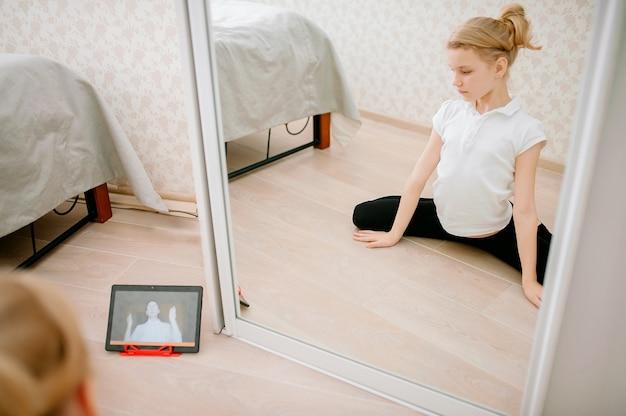 Vrij jong meisje in sportkleding kijken naar online video op laptop en fitness oefeningen thuis doen.